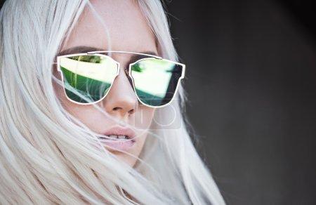 Beautiful blonde girl in green sunglassses outdoor