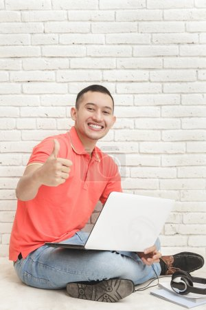 student with laptop giving thumbs up