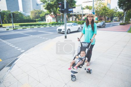 bébé dans la poussette sur le trottoir rue