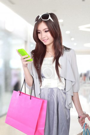 Photo pour Happy young woman using mobile phone during going shopping in the mall - image libre de droit