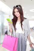 woman happy with mobile phone and shopping bags