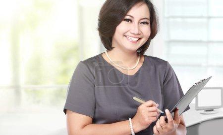 Photo pour Portrait d'une femme d'affaires d'âge moyen tenant un presse-papiers - image libre de droit