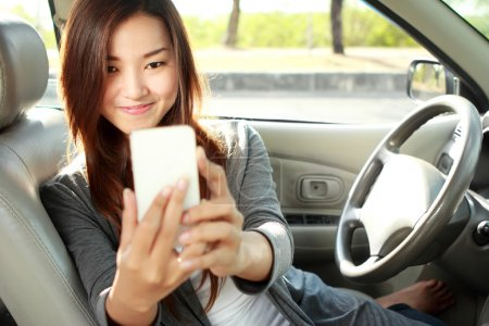young woman taking selfie in the car