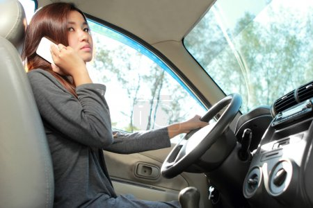 young woman talking on the phone while driving