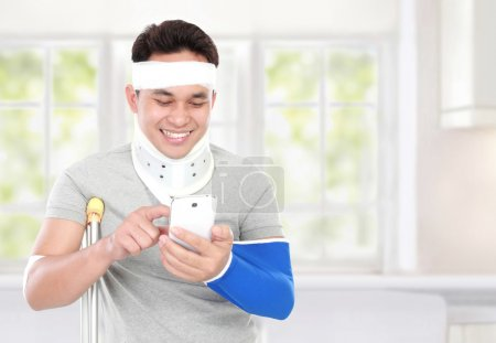 Injured young man look happy play smartphone