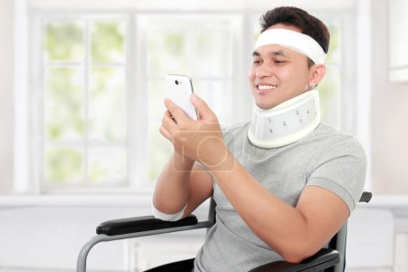 injured young man in wheelchair play on his smartphione