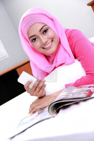 young muslim woman reading a magazine