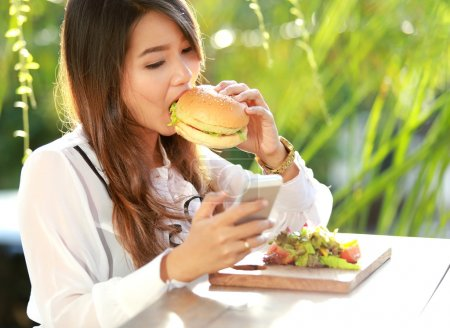 multitasking woman having lunch while texting on her mobilephone