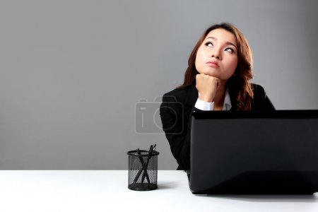 Young businesswoman  daydreaming in front of a laptop