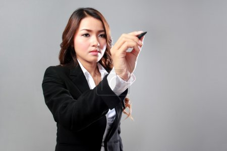 Young businesswoman writing on a virtual screen
