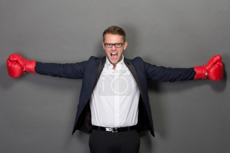 Young businessman with boxing gloves, scream