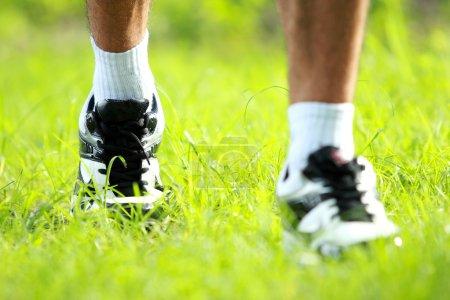 Runner feet running on grass closeup on shoe