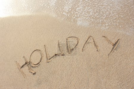"sand beach with ""holiday"" word"
