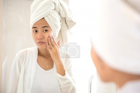Young Asian woman taking care of her face