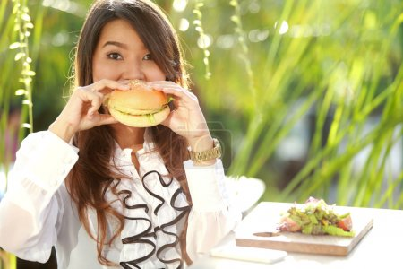 attractive woman biting a burger