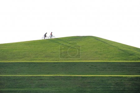 beautiful hill landscape with two people riding bicycle