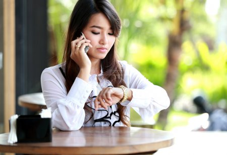 woman talking on mobile phone while looking at her wristwatch