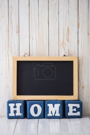 Chalkboard and HOME sign made of wooden blocks on wooden backgro