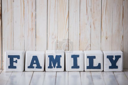 FAMILY sign made of wooden blocks on wooden background