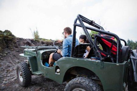Mixed couple riding a jeep