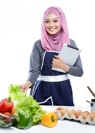young  woman wearing hijab reading cooking recipe on tablet whil