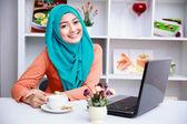 Atraktivní mladé muslimské ženy těší šálek čaje při používání