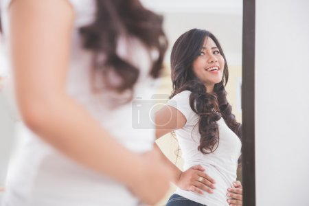 Woman looking her image on the mirror