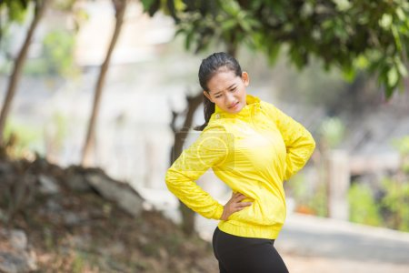Young asian woman exercising outdoor in yellow neon jacket, inju