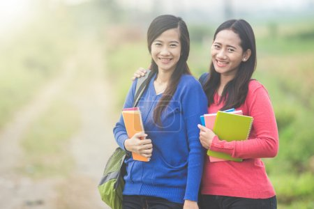 Two young Asian students holding books, smiling brightly to the