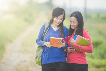 Two young Asian students reading something on the book