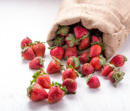 burlap sack with strawberries spilling out