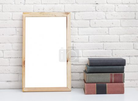 Photo for Portrait of blank white board and stack of books on table with white brick wall on the background - Royalty Free Image