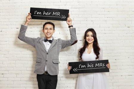 handsome groom and beautiful bride smiling while holding board