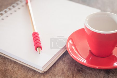 Red mug with open notebook