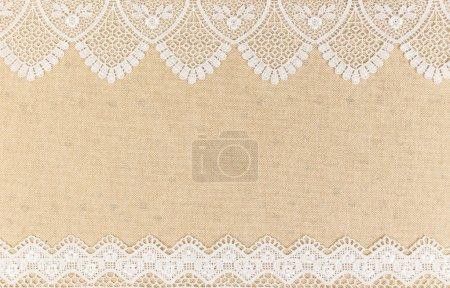 Texture de la toile de jute avec de la dentelle blanche sur le design de fond de table en bois