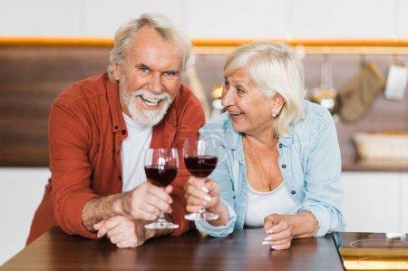 Photo pour Heureux conjoints âgés aux cheveux gris en tenue décontractée stand dans la cuisine avec du vin dans les mains et regarder la caméra et rire - image libre de droit
