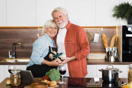 Photo pour Heureux époux âgés souriants debout dans la cuisine avec un cadeau dans les mains de ce que le mari a donné à sa femme - image libre de droit