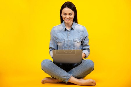 Beautiful young caucasian smiling woman in casual denim outfit, sitting on isolated orange background and working online on her laptop, replies to email, types a message