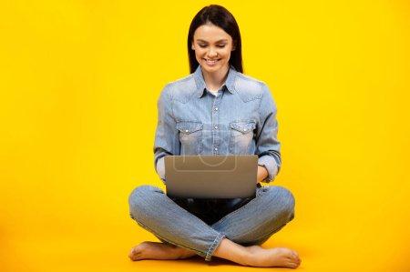 Hermosa joven caucásica sonriente mujer en traje de mezclilla casual, sentado en un fondo naranja aislado y trabajando en línea en su computadora portátil, respuestas al correo electrónico, escribe un mensaje