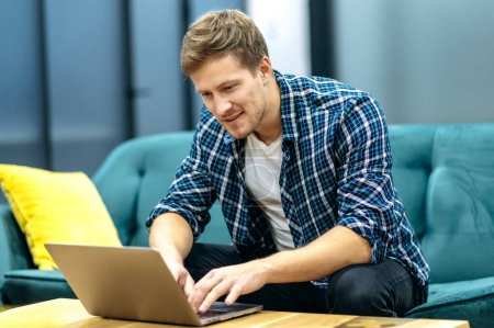 .Handsome caucasian guy freelancer uses laptop. Smiling attractive guy in stylish casual wear sits on a sofa in a creative office, browsing internet, replies to email, searching ideas.