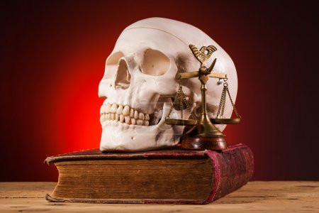 Human scull  scales of justice and old book