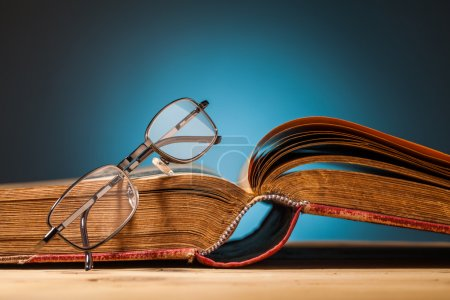 Photo for Old book and glasses on wooden table and blue background - Royalty Free Image