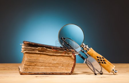 book  magnifying glass  and  glasses on wooden table
