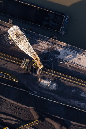 aerial view of moving crane with a heap of coal next to the coal