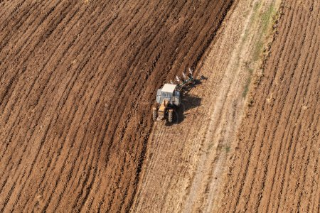 Photo for Aerial view of harvest fields with tractor in Poland - Royalty Free Image