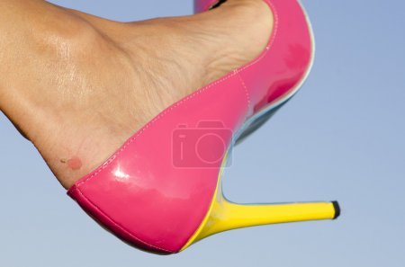 Photo pour Close up of female foot in pink high heel pumps and  painful looking scratch of blister on skin, with blue sky as background and copy space. - image libre de droit