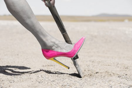 Pink high heel shovel digging in desert dirt