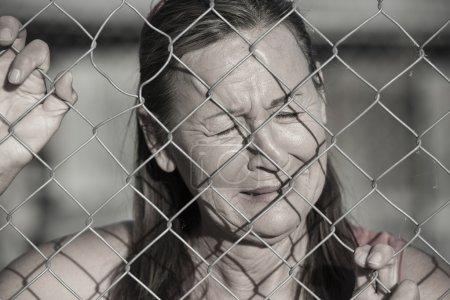 Photo pour Portrait femme pleurant derrière une clôture métallique, désespérée, dévastée, déprimée, expression faciale stressée, malheureuse, les yeux fermés . - image libre de droit