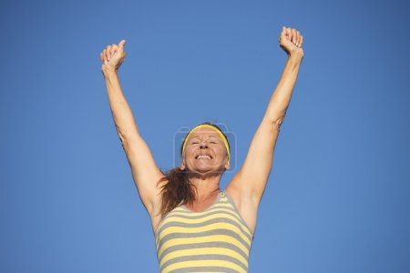 Successful fit healthy mature woman arms up