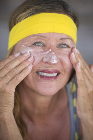 Skin care creme smiling mature woman portrait